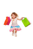 Happy little girl running and jumping with shopping bags. Royalty Free Stock Photography