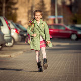 Happy little girl running  from school Stock Images
