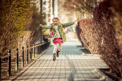 Happy little girl running  from school Royalty Free Stock Photography