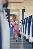 Happy little girl runs away from her mother at the train royalty free stock photo