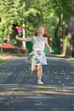 Happy little girl runs with windmill. Happy little girl with red hair in skirt runs with windmill in summer green park Stock Photo