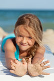 Happy little girl with sandy hands on the beach Royalty Free Stock Images