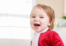 Happy little girl in a Santa costume ready for Christmas Stock Image