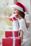 Happy little girl in Santa hat dreaming by the window holding gift Royalty Free Stock Photography