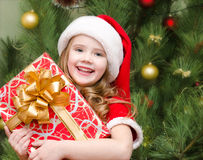 Happy little girl in santa hat with gift box Royalty Free Stock Image