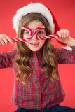 Happy little girl in santa hat holding candy canes Royalty Free Stock Images