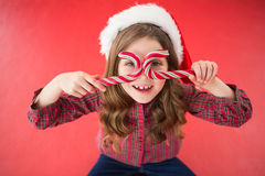 Happy little girl in santa hat holding candy canes. On red background Royalty Free Stock Photo