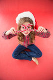 Happy little girl in santa hat holding candy canes. On red background Royalty Free Stock Images