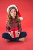 Happy little girl in santa hat holding gift. On red background Stock Images
