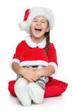 Happy little girl in Santa hat laughs on a white Royalty Free Stock Image