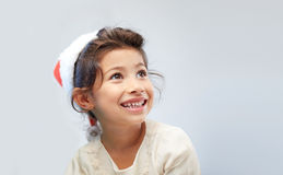 Happy little girl in santa hat over gray Royalty Free Stock Image