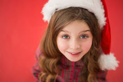 Happy little girl in santa hat. On red background Stock Photo