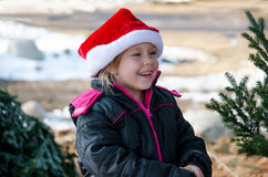 Happy little girl in a Santa hat. A happy little girl in a red Santa hat smiles while outdoors at a Christmas tree farm Stock Photography