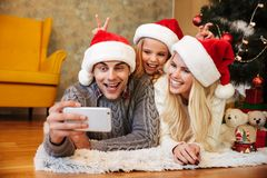 Happy little girl in Santa`s hat makes horns to her parents whil Royalty Free Stock Photography