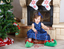 Happy little girl in santa shoes have a christmas. Stock Photos