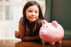 Happy little girl saving some money Royalty Free Stock Images