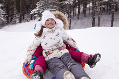 Happy little girl screams with delight, rolling with snow hill. Stock Photography