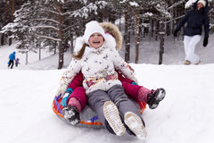 Happy little girl screams with delight, rolling with snow hill. Royalty Free Stock Photography