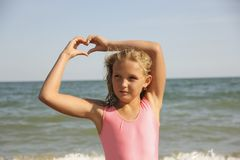 Little girl on the sea hands on the heart Royalty Free Stock Photos