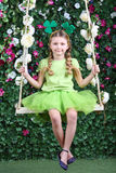 Happy little girl with shamrocks on head in green sit on swing Stock Photo
