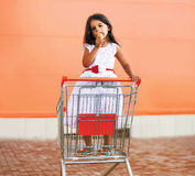 Happy little girl in shopping cart with tasty ice cream Royalty Free Stock Image