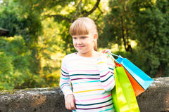 Happy little  girl  after shopping in the park Royalty Free Stock Photo