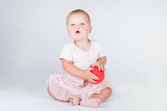 Happy little girl in a short pink dress throws Royalty Free Stock Photo