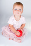 Happy little girl in a short pink dress throws Royalty Free Stock Photography