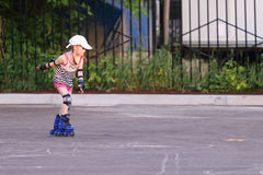 Happy little girl in shorts roller skates Royalty Free Stock Photography