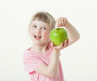 Happy little girl showing a green apple Royalty Free Stock Image