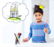 Happy little girl showing pencil or crayon Stock Photo