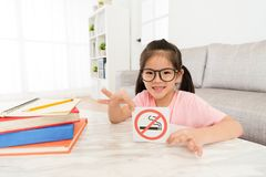 Happy little girl showing quit smoking symbol sign. Smiling happy little girl showing quit smoking symbol sign Royalty Free Stock Photos