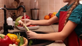 Happy little girl singing at the kitchen sink stock video footage