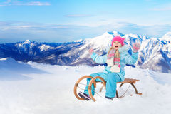 Happy little girl sit on sledge in mountains Royalty Free Stock Photography