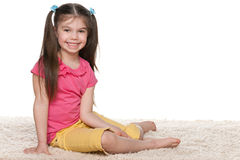 Happy little girl sits on the white carpet Royalty Free Stock Photos