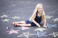 Happy little girl sitting on asphalt with painted stars royalty free stock image