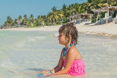 Happy little girl sitting in azure tranquil ocean on sunny gorgeous tropical beach Stock Image