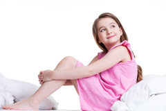 Happy little girl sitting on the bed and looking up. Royalty Free Stock Photography