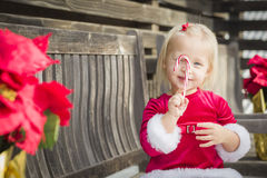 Happy Little Girl Sitting On Bench with Her Candy Cane Royalty Free Stock Photo