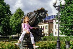 Happy little girl sitting on bronze sculpture of clown Stock Photo