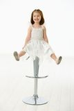 Happy little girl sitting on chair Stock Photos