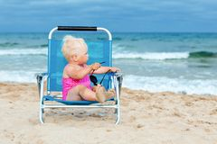 Happy little girl sitting on chair at beach Stock Photos