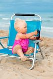 Happy little girl sitting on chair at beach Stock Images