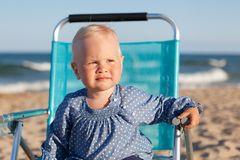 Happy little girl sitting on chair at beach Royalty Free Stock Photography