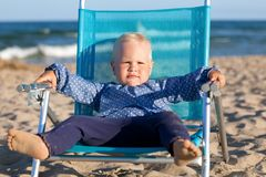 Happy little girl sitting on chair at beach Stock Photography