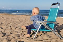 Happy little girl sitting on chair at beach Royalty Free Stock Photo