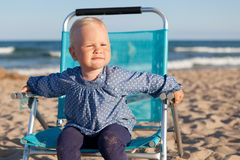 Happy little girl sitting on chair at beach Stock Photo