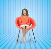 Happy little girl sitting on designer chair Stock Images