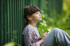 Happy little girl sitting and dreaming Royalty Free Stock Images
