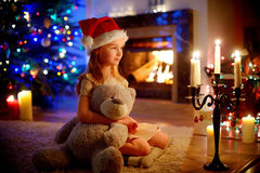 Happy little girl sitting by a fireplace on Christmas eve Stock Photography